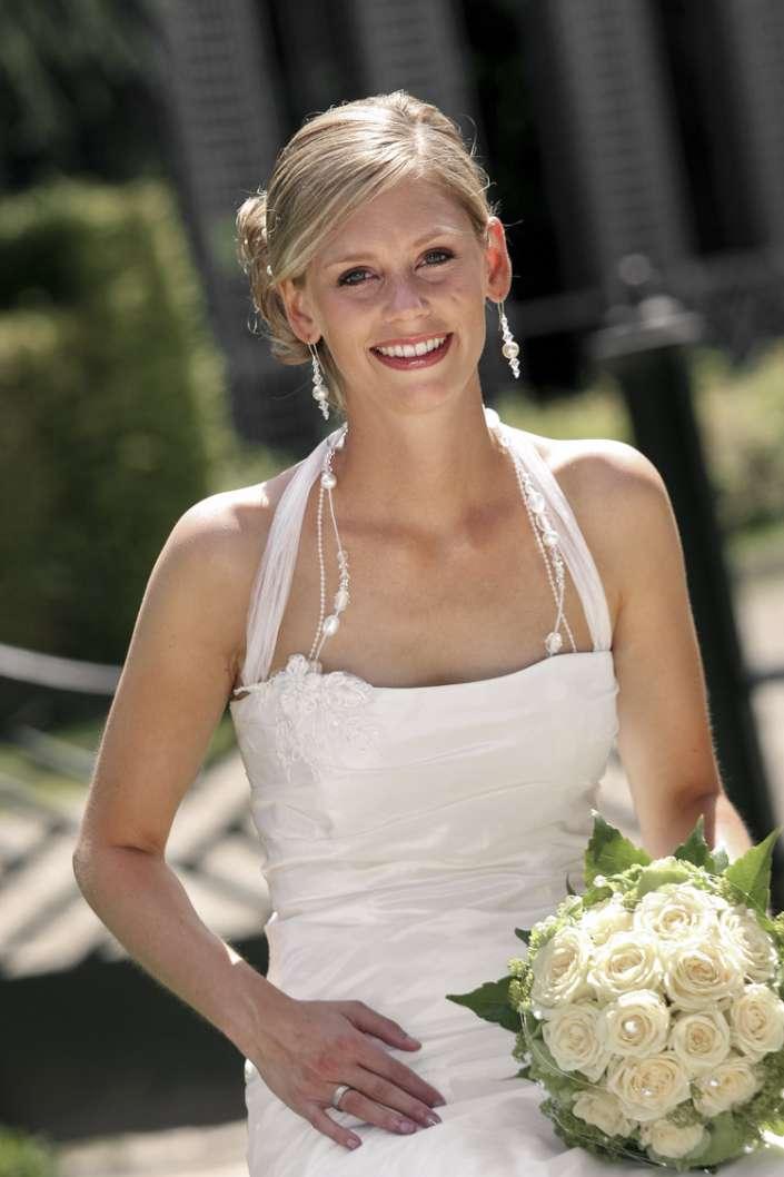 Eine hübsche blonde Braut schaut in die Kamera